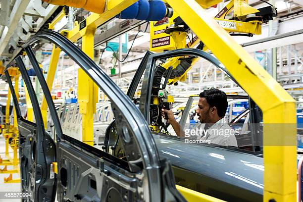 An employee moves a door of a Mahindra Mahindra Ltd XUV 500 sportutility vehicle on the production line at the company's facility in Chakan...