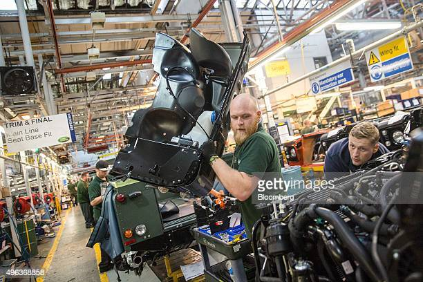 An employee moves a headlight panel to fit onto a Land Rover Defender automobiles at Tata Motors Ltd's Jaguar Land Rover vehicle manufacturing plant...