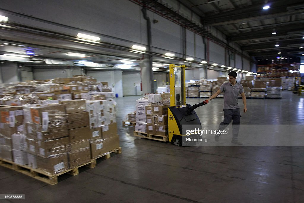 An employee moves a pallet of boxed pharmaceutical products for distribution at the Cofares SA logistical plant in Guadalajara, Spain, on Wednesday, Jan. 30, 2013. Madrid, the second-biggest contributor to Spain's economy after Catalonia, has sliced 1 billion euros from its budget in 2012, increasing public-transportation costs and university fees, cutting jobs, delaying investments and reducing health-care and social benefits. Photographer: Angel Navarrete/Bloomberg via Getty Images