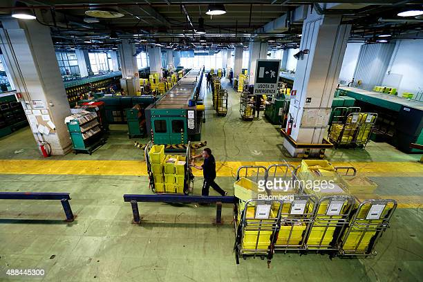 An employee moves a trolley loaded with crates inside a Poste Italiane SpA postal sorting office in Fiumicino near Rome Italy on Tuesday Sept 15 2015...