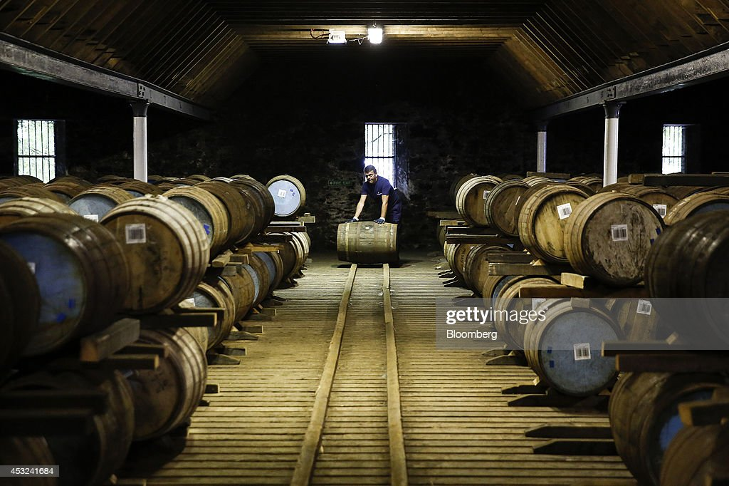An employee moves a wooden cask of Chivas Regal blended Scotch whisky, produced by Pernod Ricard SA, at the company's Strathisla distillery in Keith, U.K., on Tuesday, Aug. 5, 2014. Scottish nationalist leader Alex Salmond and former Chancellor of the Exchequer Alistair Darling, who leads the 'No' campaign, clashed over the risks and merits of independence six weeks before the Sept. 18 referendum that could bring an end to the U.K. Photographer: Simon Dawson/Bloomberg via Getty Images