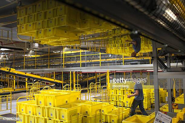 An employee moves crates at the Amazoncom Inc fulfillment center in Poznan Poland on Friday June 12 2014 Amazon is the largest distributor of ebooks...