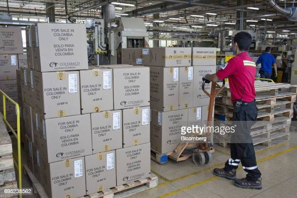 An employee moves stacks of boxes containing cigarettes ready for shipment at the Philip Morris International Coltabaco SAS production facility in...