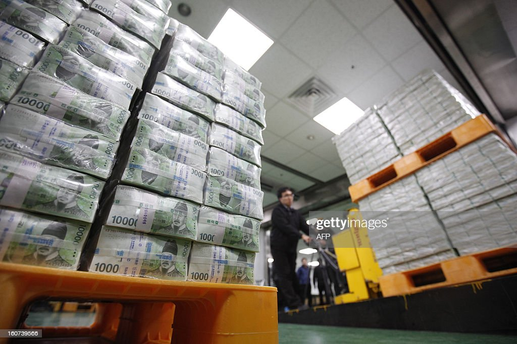 An employee moves stacks of South Korean won for delivery to commercial banks at the Bank of Korea's headquarters in Seoul on February 5, 2013. Cash demand usually picks up ahead of the Lunar New Year holiday, which begins February on 10, as companies give out special cash bonuses to their employees and parents give money to their children. AFP PHOTO / POOL / Kim Hong-Ji