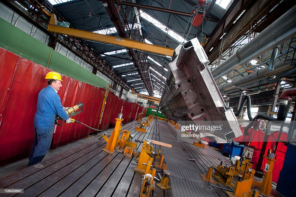 An employee moves the body shell of a highspeed Pendolino train at Alstom SA's trainbuilding unit in Savigliano Italy on Friday Feb11 2011 Alstom SA...
