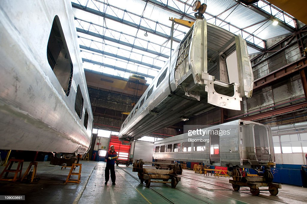 An employee moves the body shell of a highspeed Pendolino train center at Alstom SA's trainbuilding unit in Savigliano Italy on Friday Feb11 2011...