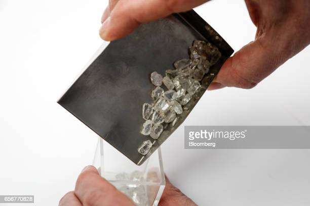 An employee moves unpolished diamonds at the De Beers SA headquarters on Charterhouse Street in London UK on Wednesday Feb 1 2017 Number 17...