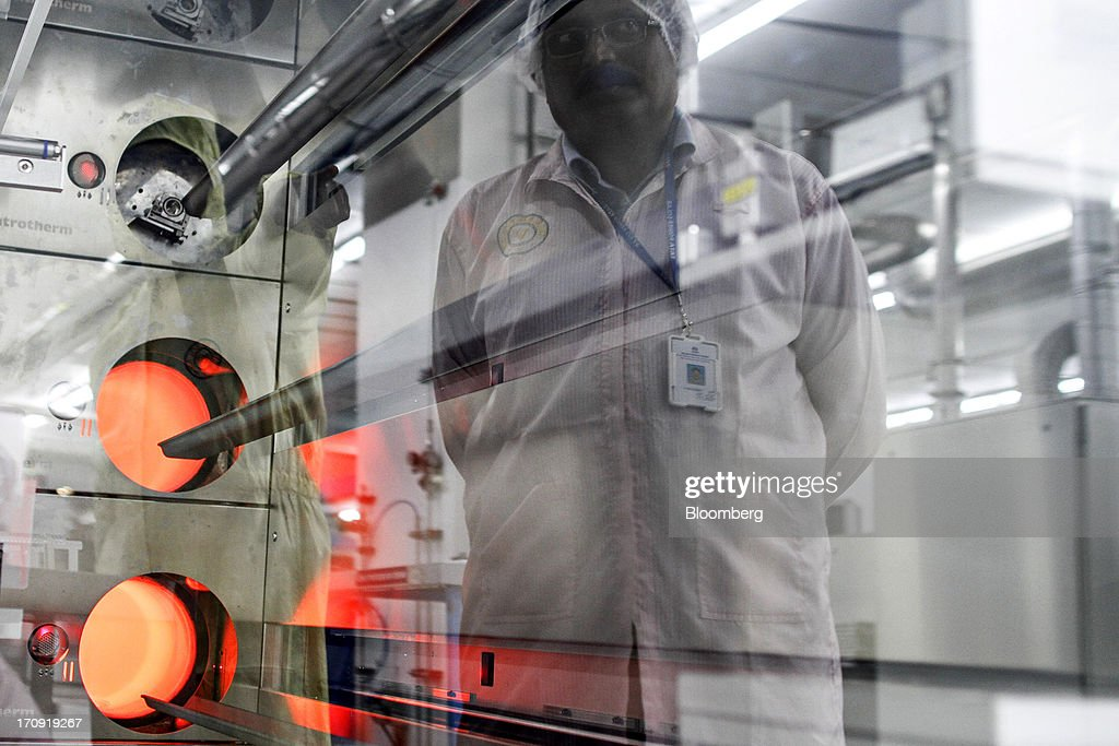 An employee observing solar cells in a diffusion furnace is reflected in the machine's window on the cell production line at the Tata Power Solar Systems Ltd. manufacturing plant in Bangalore, India, on Tuesday, June 11, 2013. Tata Groups solar unit is expanding its business building plants for customers, forecasting that offices and factories will be paying more for grid power than solar by 2016 in most Indian states. Photographer: Dhiraj Singh/Bloomberg via Getty Images