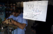 An employee of a business closed during a blackout stands behind the door with a notice reading 'There's No Light' in Caracas on September 3 2013...