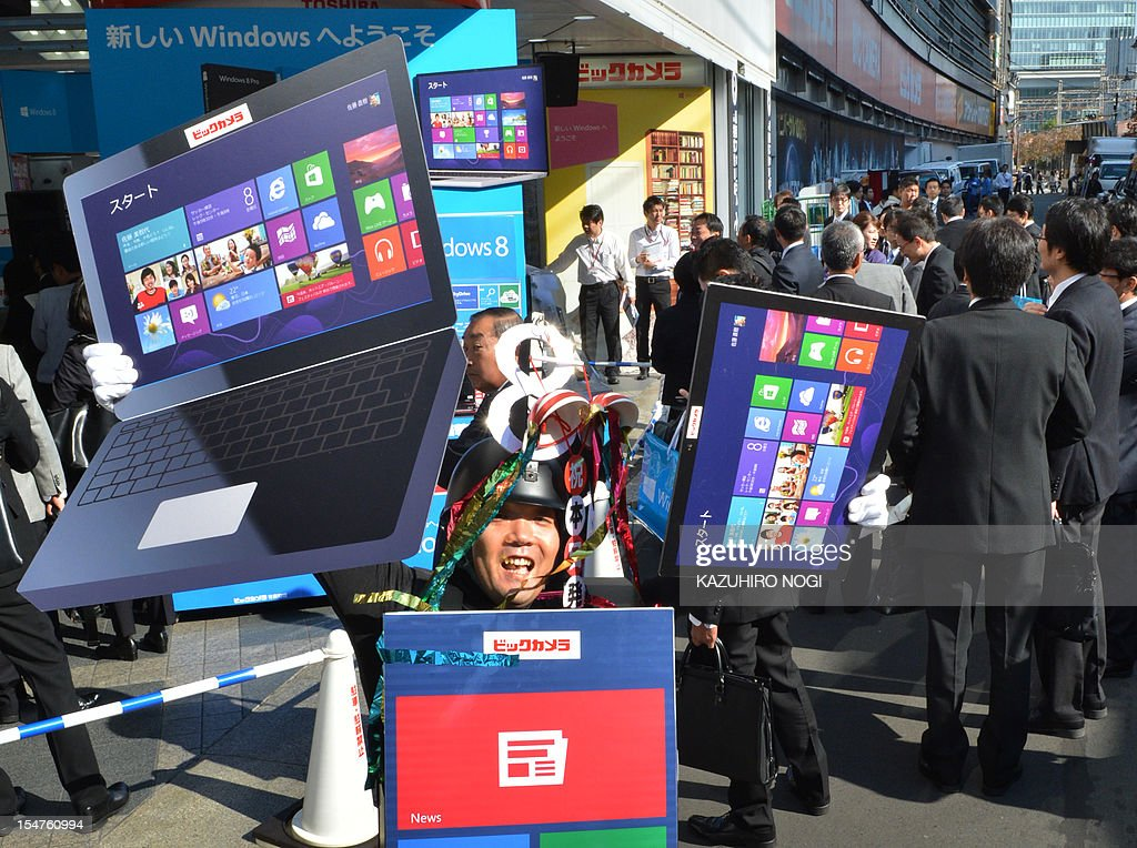 An employee of a camera chain promotes the release of Microsoft's new Windows 8 operating system in Tokyo on October 26, 2012. Microsoft announced that Windows 8 would launch on October 26 in 37 languages and 140 worldwide markets. AFP PHOTO / KAZUHIRO NOGI