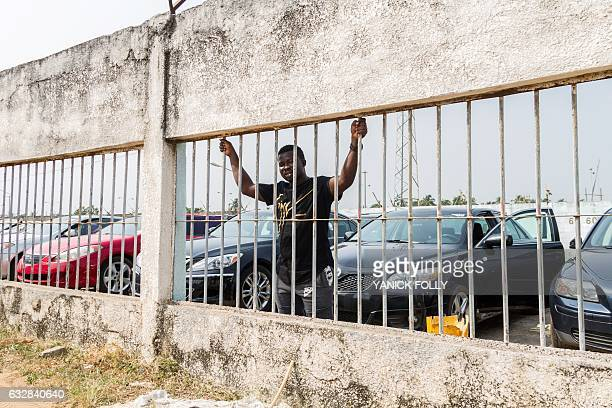 An employee of a car park outside Cotonou waits for customers on January 12 2017 Benin's car market began its free fall last year while the Nigerian...