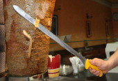 An employee of a Doener kebab stand cuts meat for Doener sandwiches on February 23 2013 in Berlin Germany The Europewide scandal over the...