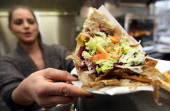 An employee of a Doener kebab stand serves a Doener sandwich on February 23 2013 in Berlin Germany The Europewide scandal over the contamination of...
