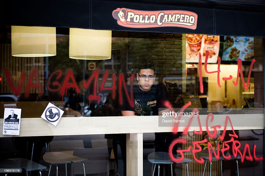 An employee of a fast food restaurant looks through the shop's window which has been sprayed with 'Vaga General', 'General Strike' in Catalan, after members of a picket forced the restaurant to close during a 24-hour strike on November 14, 2012 in Barcelona, Spain. Spain's trade unions have called the second general strike during Mariano Rajoy's presidency. With the country's unemployment rate set at 25 per cent, demonstrators from social movements are expected to join striking public sector workers to protest against austerity cuts and labour reforms.