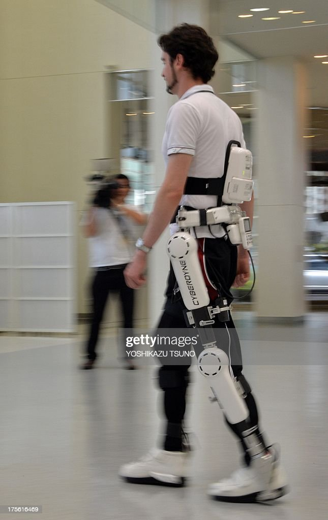 An employee of a Japanese robot venture demonstrates new robot suit Hybrid Assistive Limb (HAL) for medical use, developed by University of Tsukuba professor Yoshiyuki Sankai, at the Cyberdyne headquarters in Tsukuba, suburban Tokyo on August 5, 2013. The HAL, which is designed to learn the user's motion and assist their movement, can be used for the rehabilitation of disabled and assist elderly people, was authenticated as a medical device in Europe by European certification authority. AFP PHOTO / Yoshikazu TSUNO