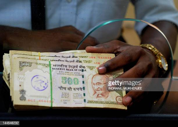 An employee of a multinational company waits to deposit Indian rupee notes at a bank in Mumbai on May 16 2012 India's rupee hit a record low against...