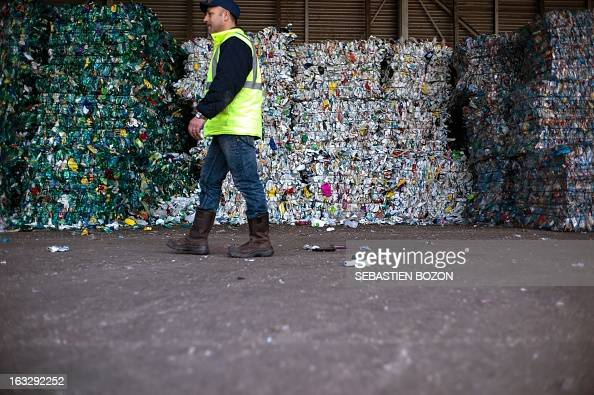 An employee of a recycling centre walks past flated plastic bottles on March 7 2013 in AspachleHaut part of waste sorting AFP PHOTO / SEBASTIEN BOZON