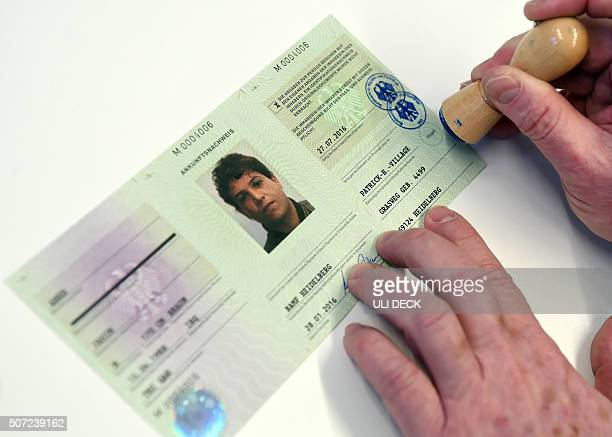 An employee of a registration centre for refugees in Heidelberg western Germany stamps a socalled 'Ankunftsnachweis' a kind of passport attesting...