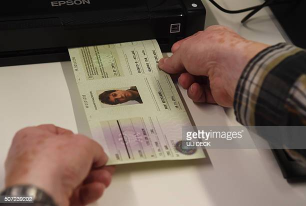 An employee of a registration centre for refugees in Heidelberg western Germany prints a socalled 'Ankunftsnachweis' a kind of passport attesting...