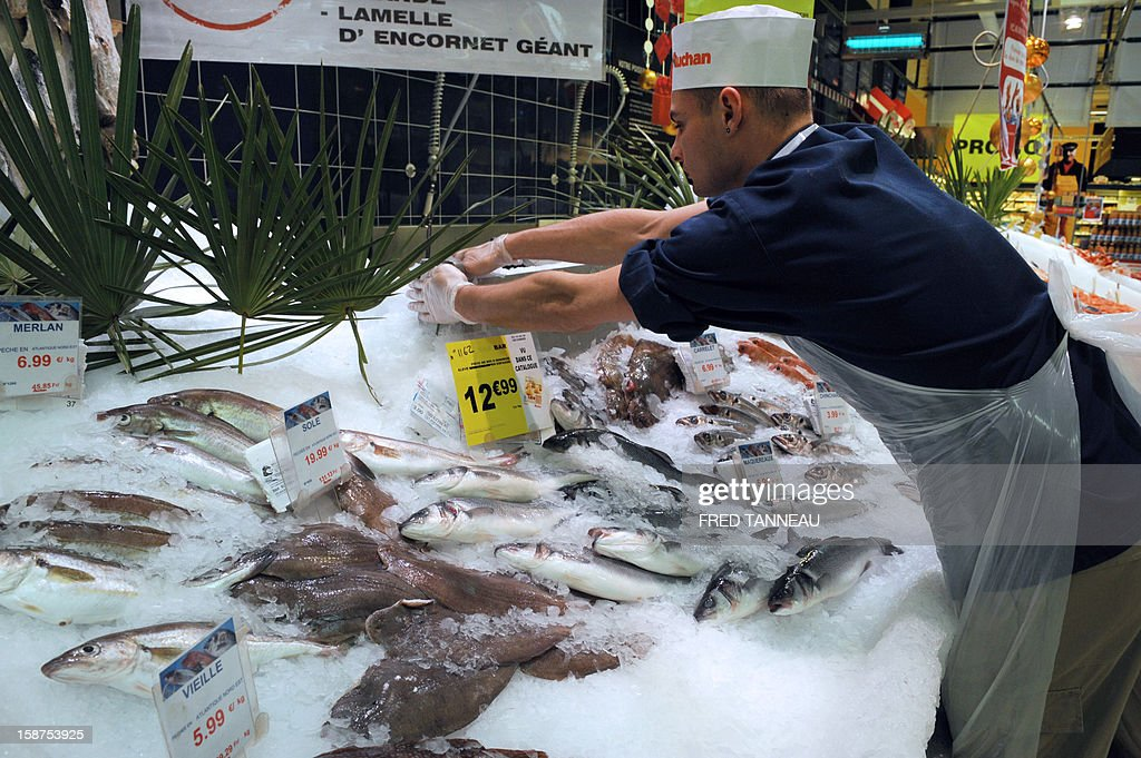 An employee of a supermarket Auchan works at a fish stand on December 27, 2012 in Saint-Sebastien-sur-Loire, western France.