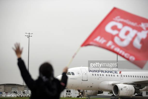 An employee of Air France waves a CGT union flag in front of an Airbus A330 at the company headquarters in RoissyenFrance on October 5 ahead the...