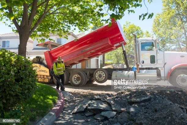 An employee of American Asphalt uses a leaf blower to clear debris near a large pile of pulverized asphalt with a red dump truck in the background...