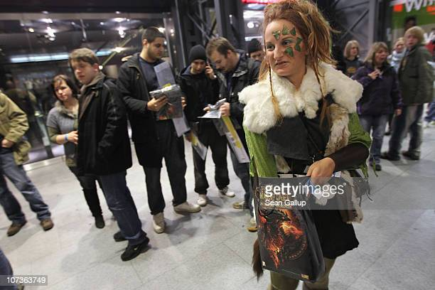 An employee of an event company dressed as a 'World of Warcraft' character distributes tshirts to video gaming enthusiasts waiting to purchase the...