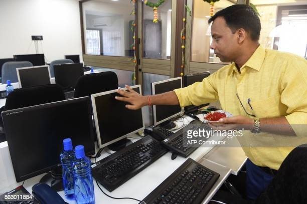 An employee of an Indian brokerage house places flowers on a trading terminal before Muhurat Trading on the occasion of Diwali Festival in Mumbai on...