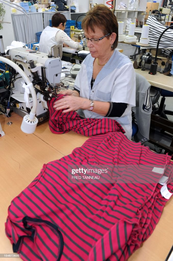 An employee of Armor Lux, specialist of the Breton style knits, works on October 24, 2012 in Quimper, western France. AFP PHOTO FRED TANNEAU