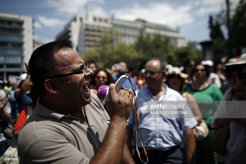 An employee of ATEbank shouts a slogan against Greek government in front of the Finance Ministry during a demonstration in Athens on August 1 2012...