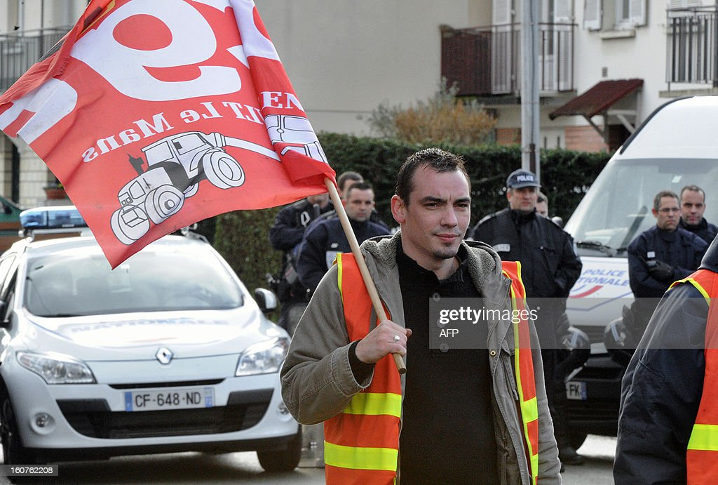 An employee of Auto Chassis International company, owned by French automaker Renault, takes part in a demonstration outside the home of the French Minister of Agriculture to protest against job cuts on February 5, 2013 in Le Mans, western France. Renault, which announced plans to cut 7,500 jobs in France through natural attrition and early retirement has pledged not to close any factories if unions agree to changes that allow the company to compete.