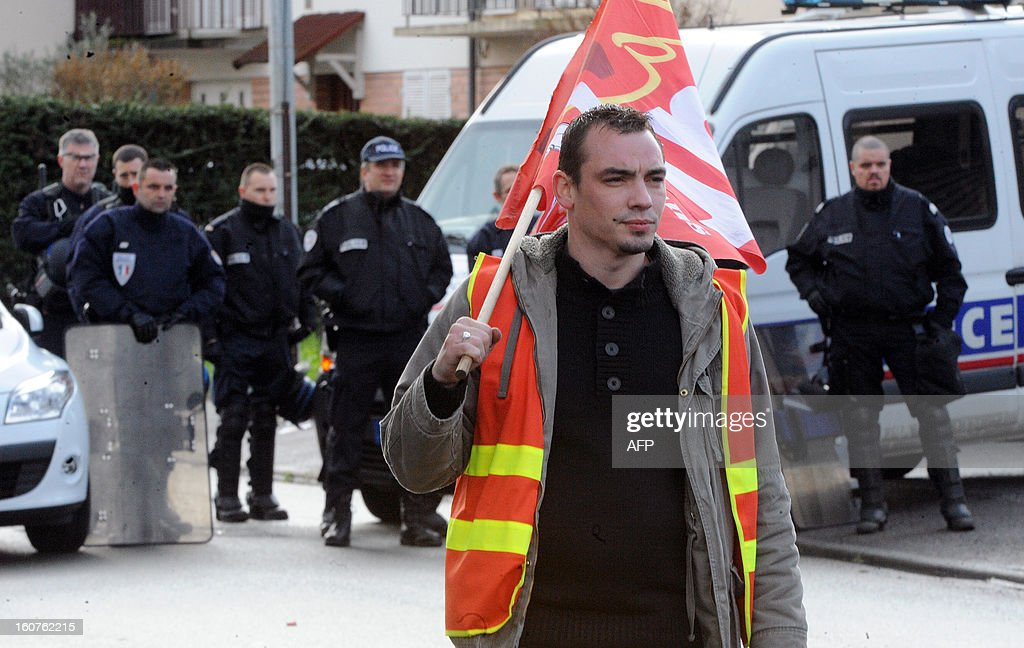 An employee of Auto Chassis International company, owned by French automaker Renault, takes part in a demonstration outside the home of the French Minister of Agriculture to protest against job cuts on February 5, 2013 in Le Mans, western France. Renault, which announced plans to cut 7,500 jobs in France through natural attrition and early retirement has pledged not to close any factories if unions agree to changes that allow the company to compete. AFP PHOTO / JEAN-FRANCOIS MONIER