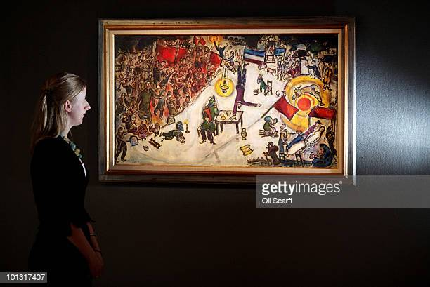 An employee of Bonhams auction house admires a painting by Marc Chagall which features in their forthcoming Impressionist and Modern Art Sale on June...