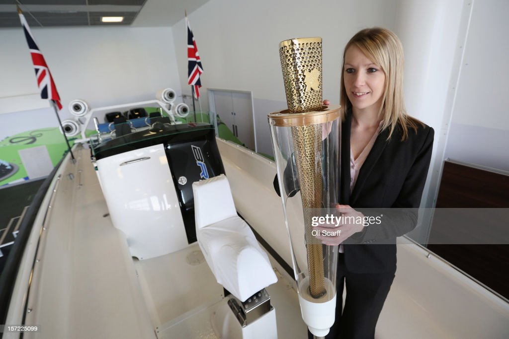 An employee of Bonhams auction house admires an Olympic torch on a Bladerunner RIB 35 Powerboat in Mercedes-Benz World on November 30, 2012 in Weybridge, England. The boat was driven by footballer David Beckham as it carried the Olympic flame to the Olympic Stadium in the opening ceremony of the London 2012 Olympic Games. The boat is due to be auctioned on December 3, 2012 and is expected to fetch 250,000 GBP..