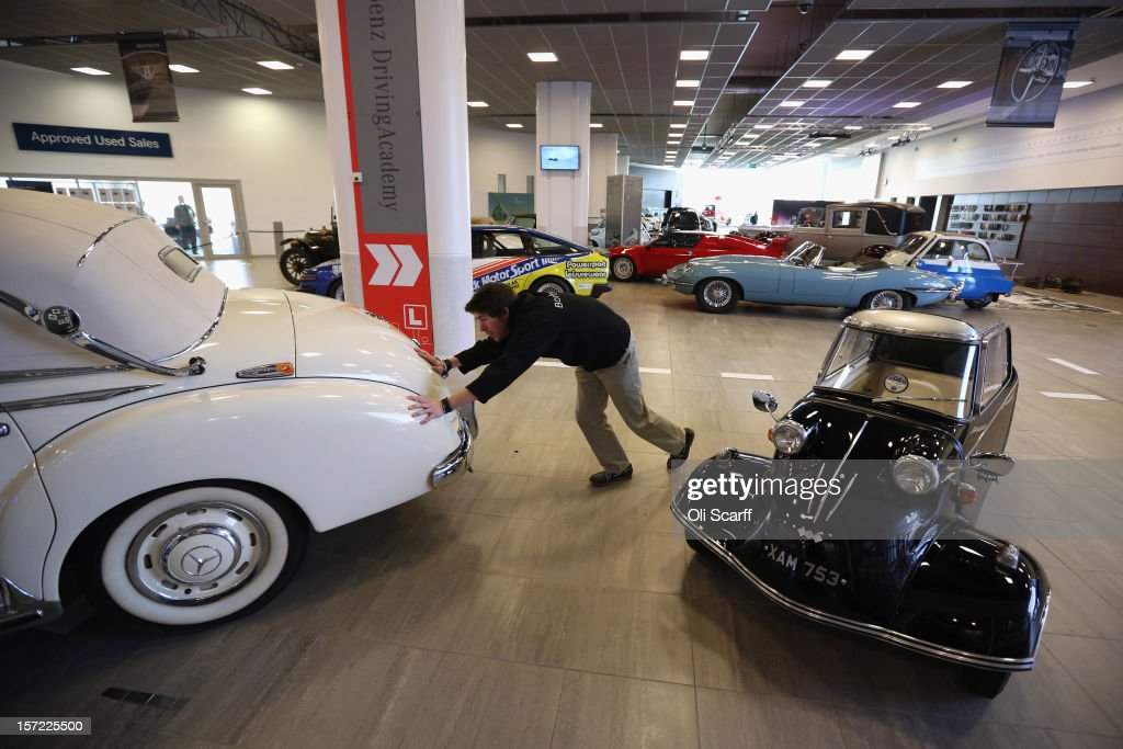 An employee of Bonhams auction house moves a 1952 Mercedes-Benz 300b past a 1960 Messerschmitt KR200, which feature in Bonhams' 'Important Motor Cars and Automobilia' auction, scheduled for Monday, December 3, 2012, in Mercedes-Benz World on November 30, 2012 in Weybridge, England. The auction also includes a Bladerunner RIB 35 Powerboat which was driven by footballer David Beckham as it carried the Olympic flame to the Olympic Stadium in the opening ceremony of the London 2012 Olympic Games.