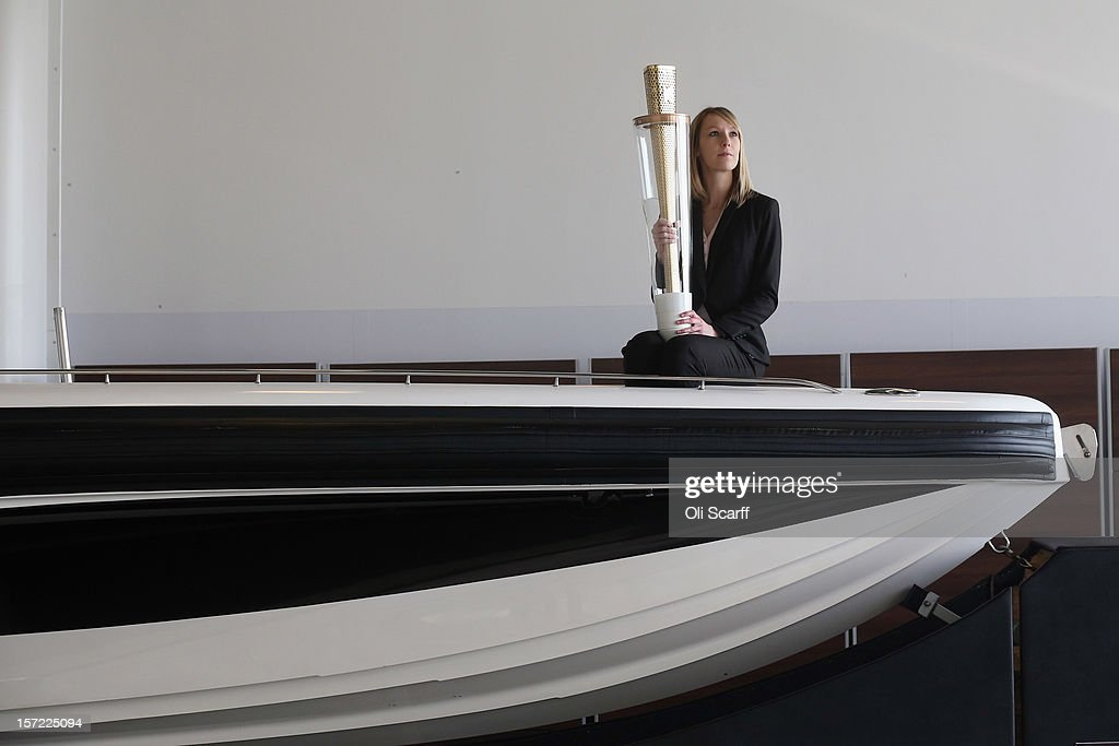 An employee of Bonhams auction house sits on a Bladerunner RIB 35 Powerboat in Mercedes-Benz World on November 30, 2012 in Weybridge, England. The boat was driven by footballer David Beckham as it carried the Olympic flame to the Olympic Stadium in the opening ceremony of the London 2012 Olympic Games. The boat is due to be auctioned on December 3, 2012 and is expected to fetch 250,000 GBP.