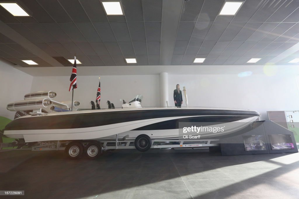 An employee of Bonhams auction house stands on a Bladerunner RIB 35 Powerboat in Mercedes-Benz World on November 30, 2012 in Weybridge, England. The boat was driven by footballer David Beckham as it carried the Olympic flame to the Olympic Stadium in the opening ceremony of the London 2012 Olympic Games. The boat is due to be auctioned on December 3, 2012 and is expected to fetch 250,000 GBP.