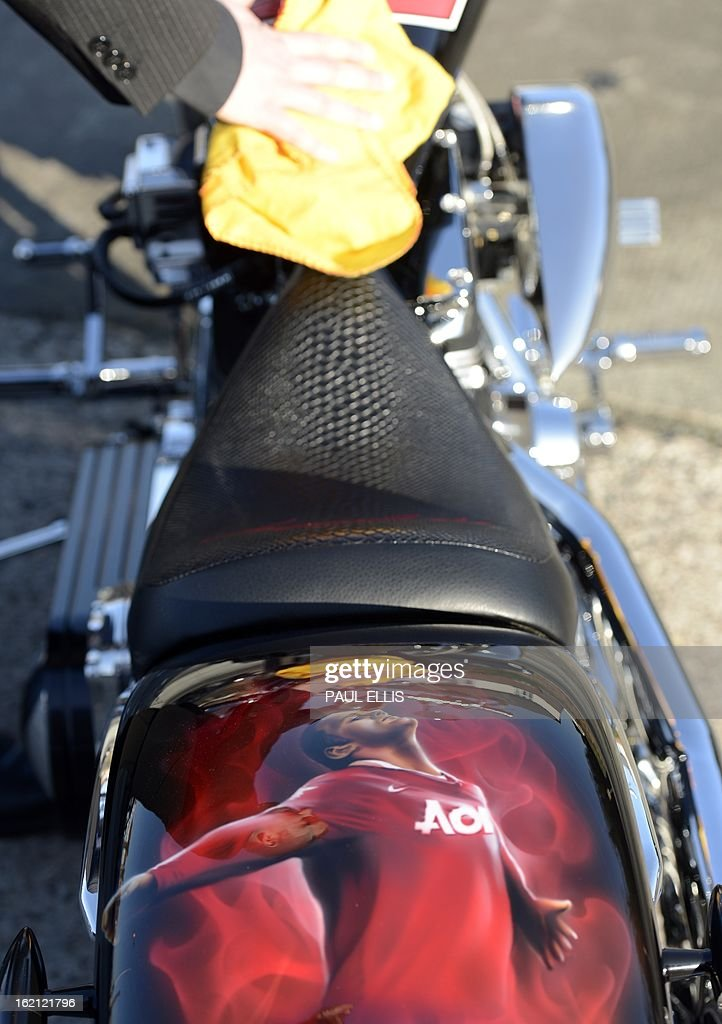 An employee of Bonhams Auction Housewipes down the tank on a motorcycle designed by Manchester United and England footballer Wayne Rooney in Chester, north west England on February 19, 2013 ahead of an auction where it is believed it could fetch between £40,000 and £60,000 in aid of charity. The 2012 Lauge Jensen cruiser-style machine, designed by the world-famous striker and custom-made by the Danish motorcycle manufacturer will go under the hammer on February 20, 2013 on behalf of KidsAid, a Danish charitable foundation that helps young people affected by illness. AFP PHOTO/Paul Ellis
