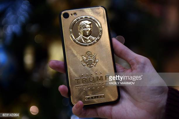 An employee of Caviar Phones a RussianItalian company specializing in smartphone customization displays a special goldplated iPhone 7 smartphone...