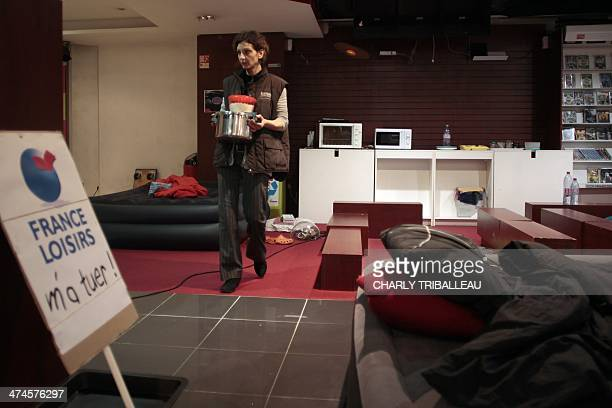 An employee of 'Chapitre' book network brings food overnight on February 24 in the shop that workers occupy in Evreux northwestern France some hours...