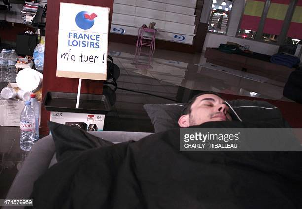 An employee of 'Chapitre' book network sleeps overnight near a board where the slogan 'killed me ' had been added to the name of France Loisirs group...