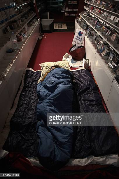 An employee of 'Chapitre' book network sleeps overnight on February 24 in the shop that workers occupy in Evreux northwestern France some hours ahead...