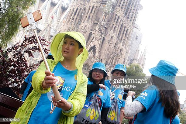 An employee of Chinese company Tiens takes a 'selfie' before a visit at the Basilica and Expiatory Church of the Holy Family in Barcelona on May 8...