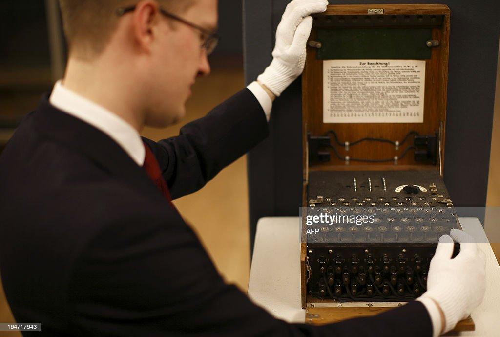 An employee of Christie's auction house poses with a German three-rotor Enigma cipher machine, circa 1939, in London on March 27, 2013 during a press preview of their April 'Travel, Science and Natural History' sale. This machine was widely used during World War II to encrypt and decode messages sent between the German military and their commanders and is estimated to fetch 40,000 - 60,000 GBP when it goes on sale on April 24, 2013.