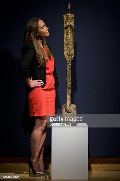 An employee of Christie's auction house poses with a sculpture entitled 'Femme de Venise II' conceived in 1956 by Swiss artist Alberto Giacometti...