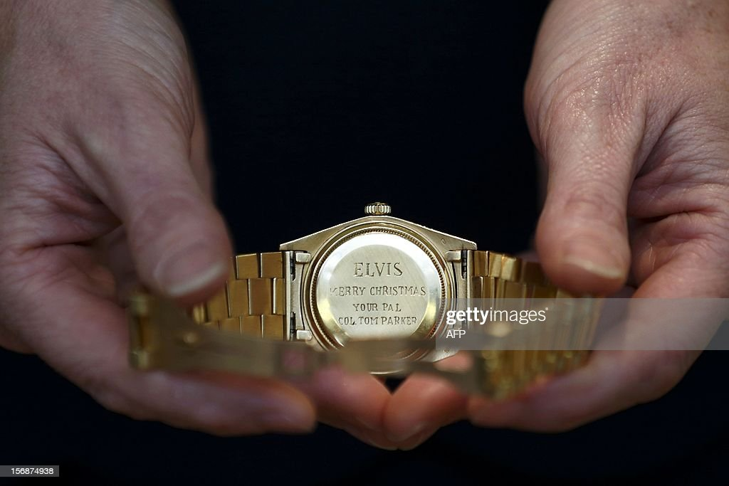 An employee of Christie's auction house poses with a1976 Rolex watch given to Elvis Presley by Colonel Tom Parker which is estimated to sell for...