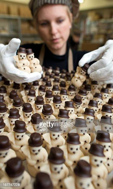 An Employee of Confiserie Felicitas GmbH prepares marzipan snowmen in Hornow eastern Germany on December 4 2012 For the production is only used pure...