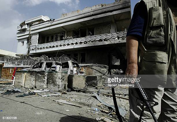 An employee of Dyncorp a US based private security company stands in front of the company's head office building recently destroyed on August 29 2004...