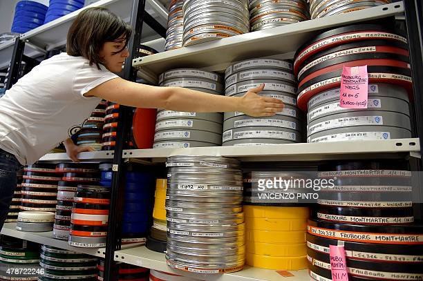 An employee of film restoration laboratory Cineteca di Bologna stacks film canisters at the laboratory in Bologna on June 25 2015 The Cineteca...
