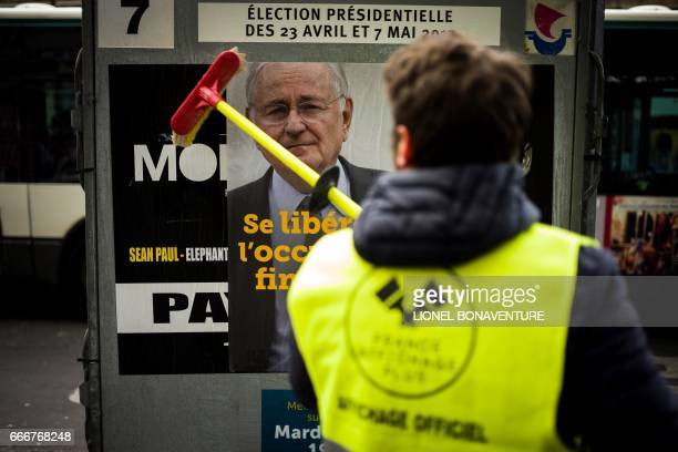 An employee of 'France Affichage Plus' puts up a campaign poster for French presidential election candidate for the Solidarite et Progres party...